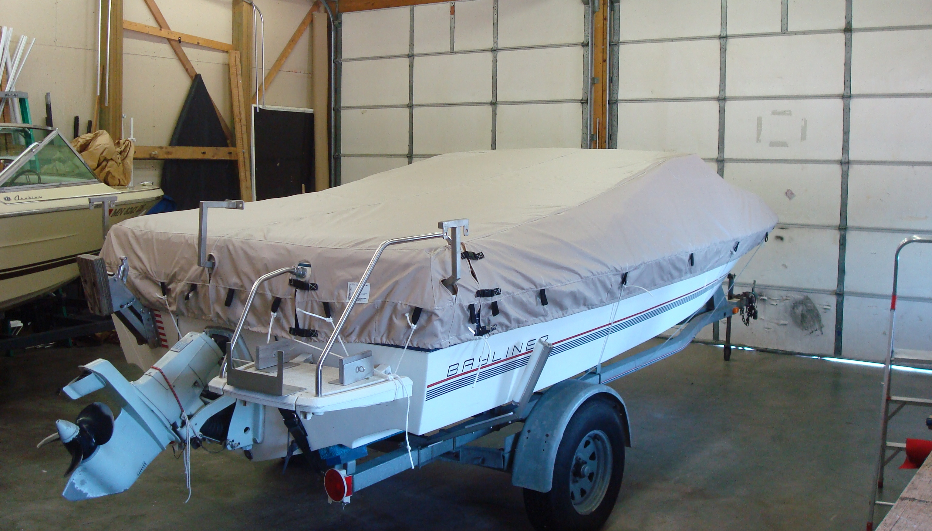 Custom Sunbrella Boat Cover: Bayliner tie down mooring cover with special velcro cutouts for ladder and hardware mounts